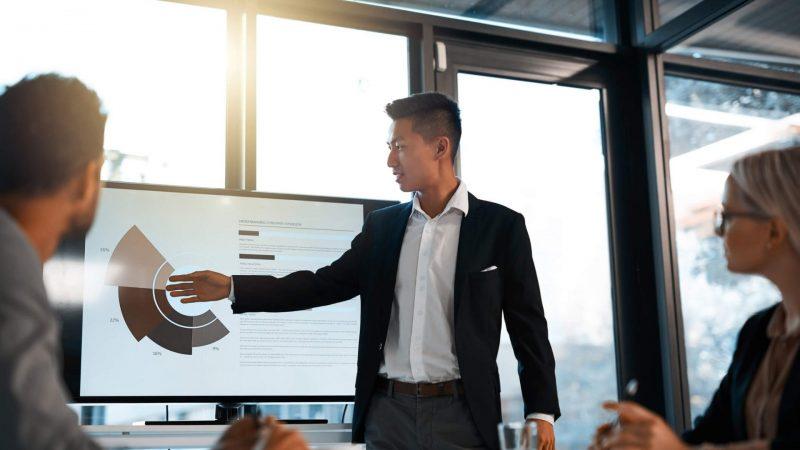 Pessoa apontando para um gráfico em uma reunião de trabalho