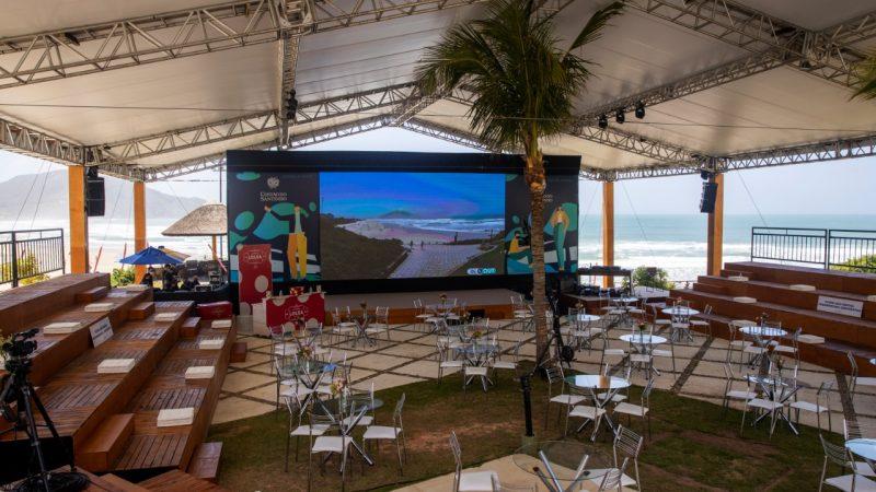 o espaço de eventos arena frente mar com telão ao fundo acima do palco e ao redor arquibancadas e mesas brancas espalhadas no meio do espaço. Ao fundo do palco e do telão o mar aparece.