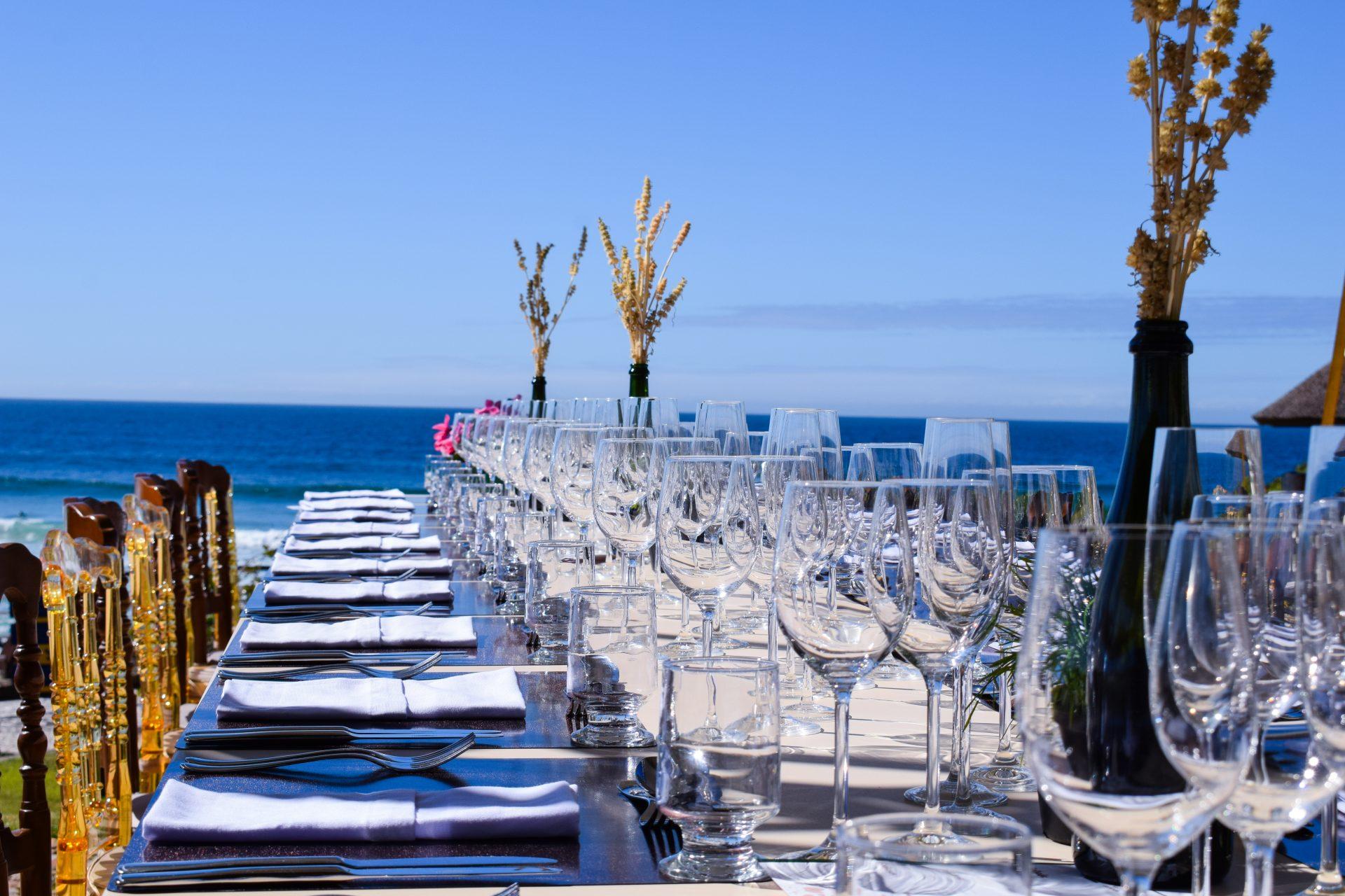 Mesa posta para um evento com taças, pratos e talheres e o mar e o céu ao fundo em tons de azul.
