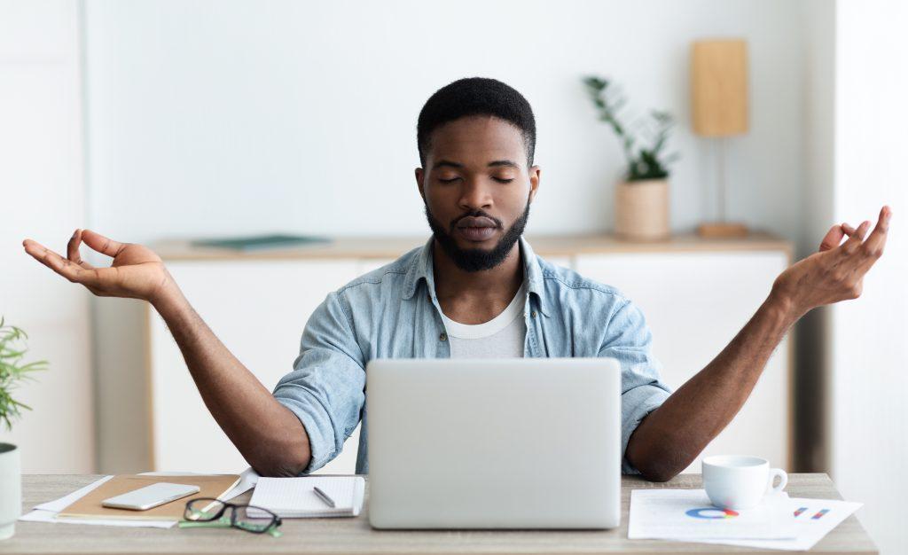 homem praticando a meditação da yoga no escritóriono escritório