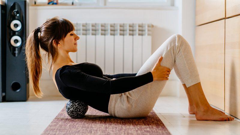mulher pratica yoga em casa